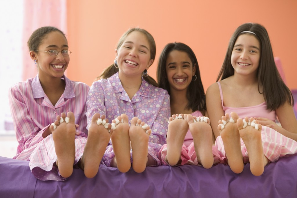 Four girls sitting on bed with bare feet