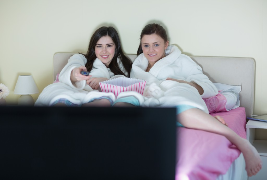 Two smiling friends wearing bathrobes watching a movie on bed at home in bedroom