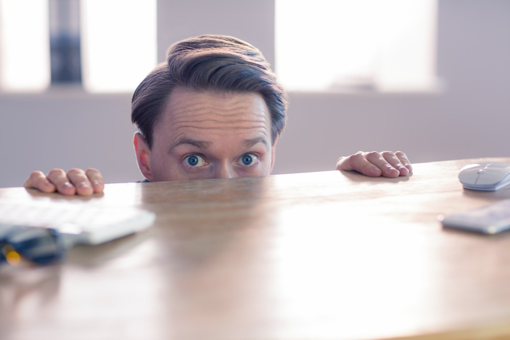 Nervous businessman peeking over desk in his office
