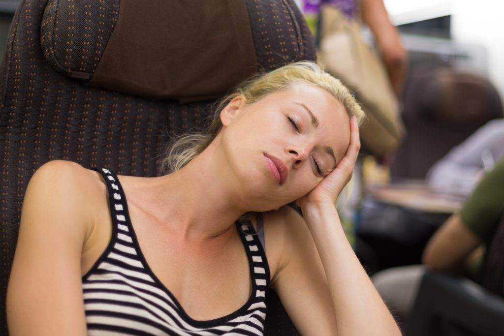 Blonde casual caucasian lady napping while traveling by train.
