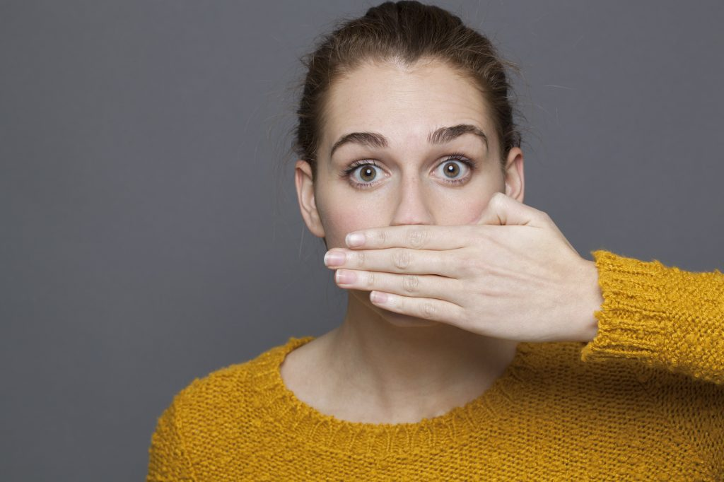 stunned young woman covering her mouth for silence