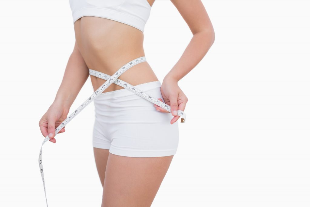 Midsection of woman measuring waist over white background