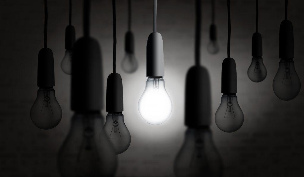Light bulb lighting up in the dark
