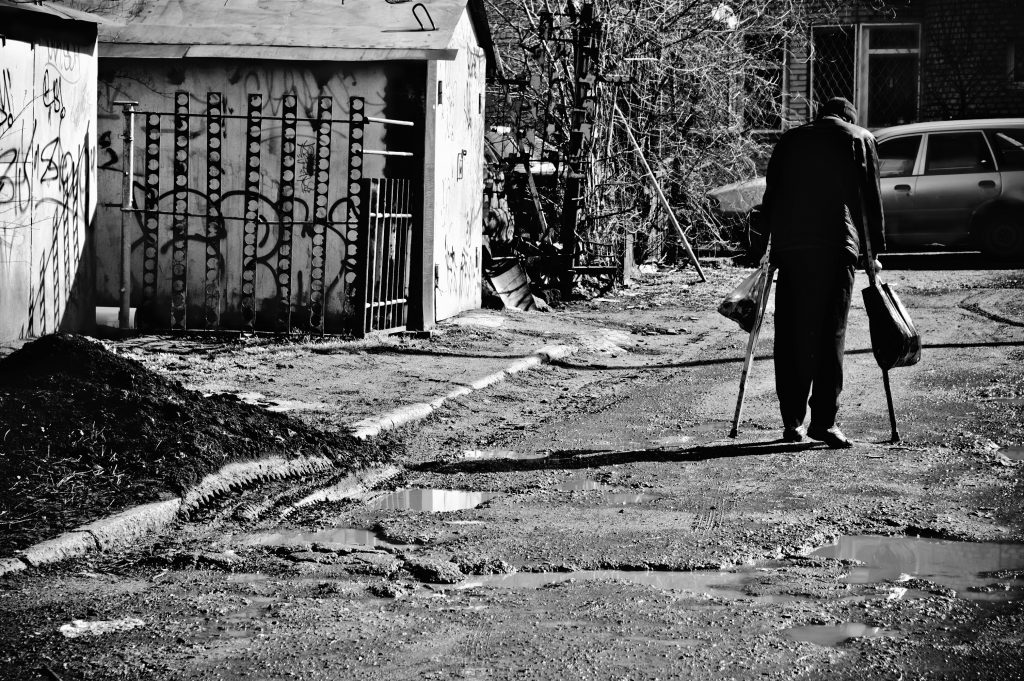 A sick poor man with crutches walking down the street. Rear view; black and white