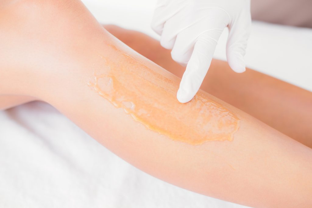 Close up side view of female leg with hot wax at spa center