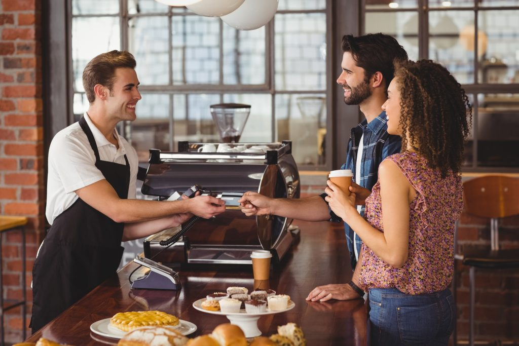 Smiling hipster giving credit card to barista at coffee shop
