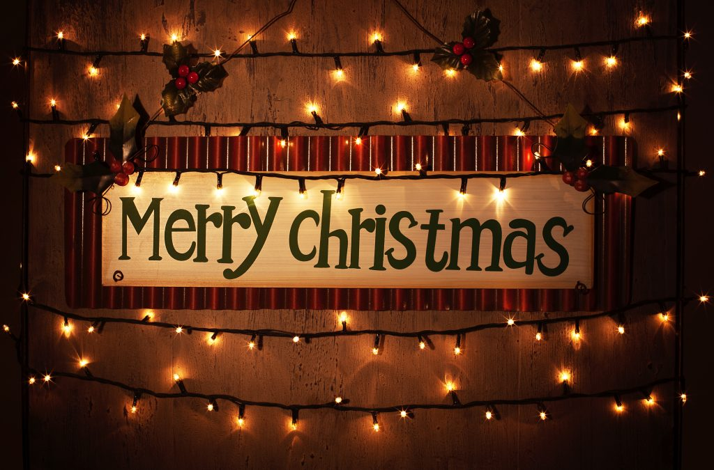 Picture of Merry Christmas banner on brown grunge door at home, happy New Year, glowing electrical garland, Christmastime house interior, congratulations postcard, holiday illumination
