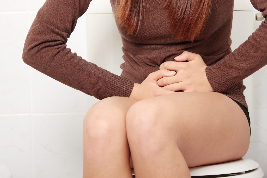 Young woman with stomach issues in her bathroom at home