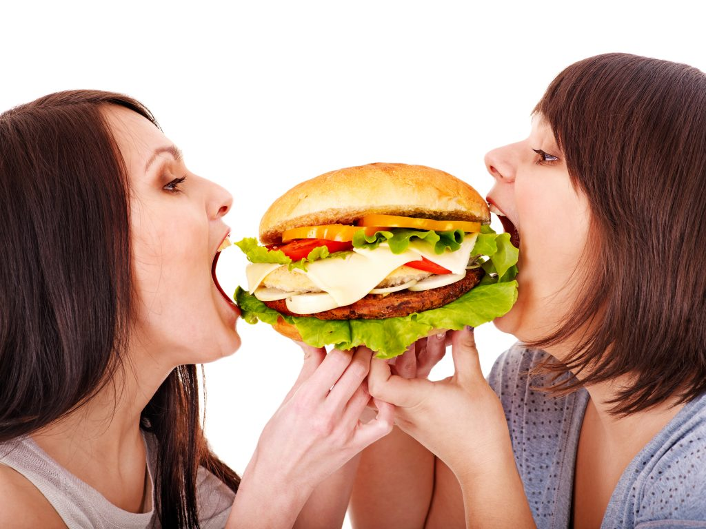 Women eating hamburger. Isolated.