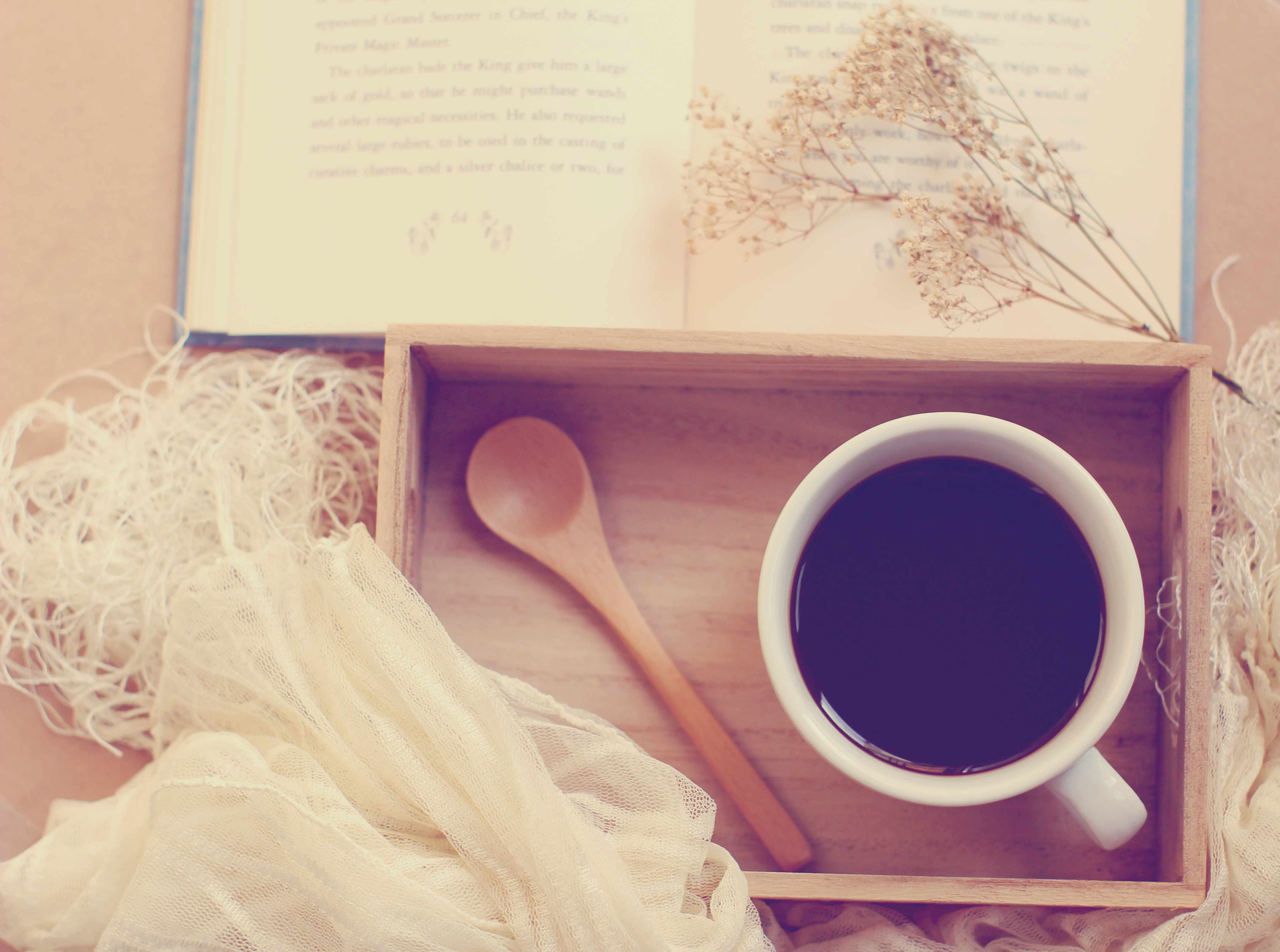 Black coffee and spoon on wooden tray with book, retro filter effect
