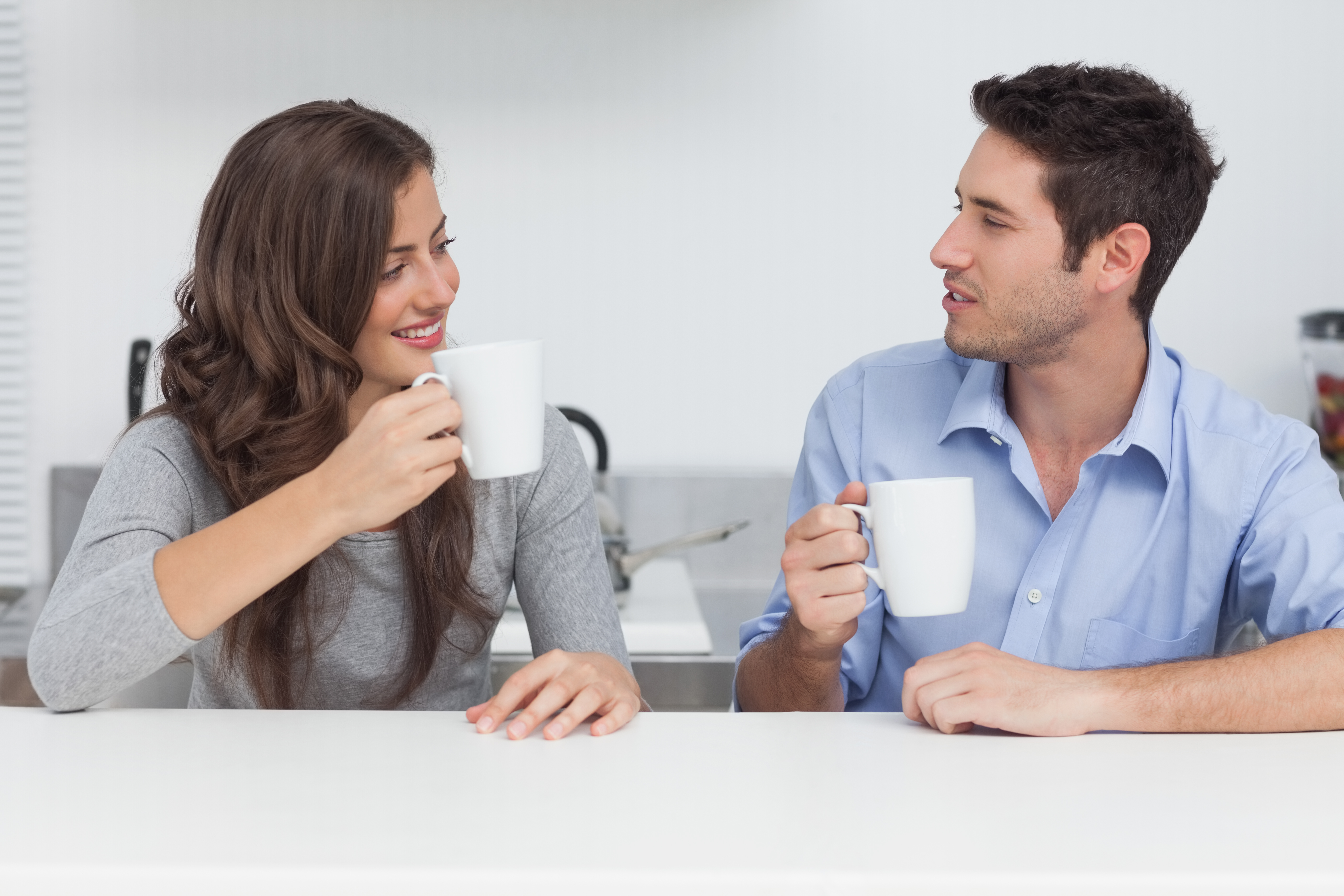 Couple drinking cups of coffee together in the kitchen
