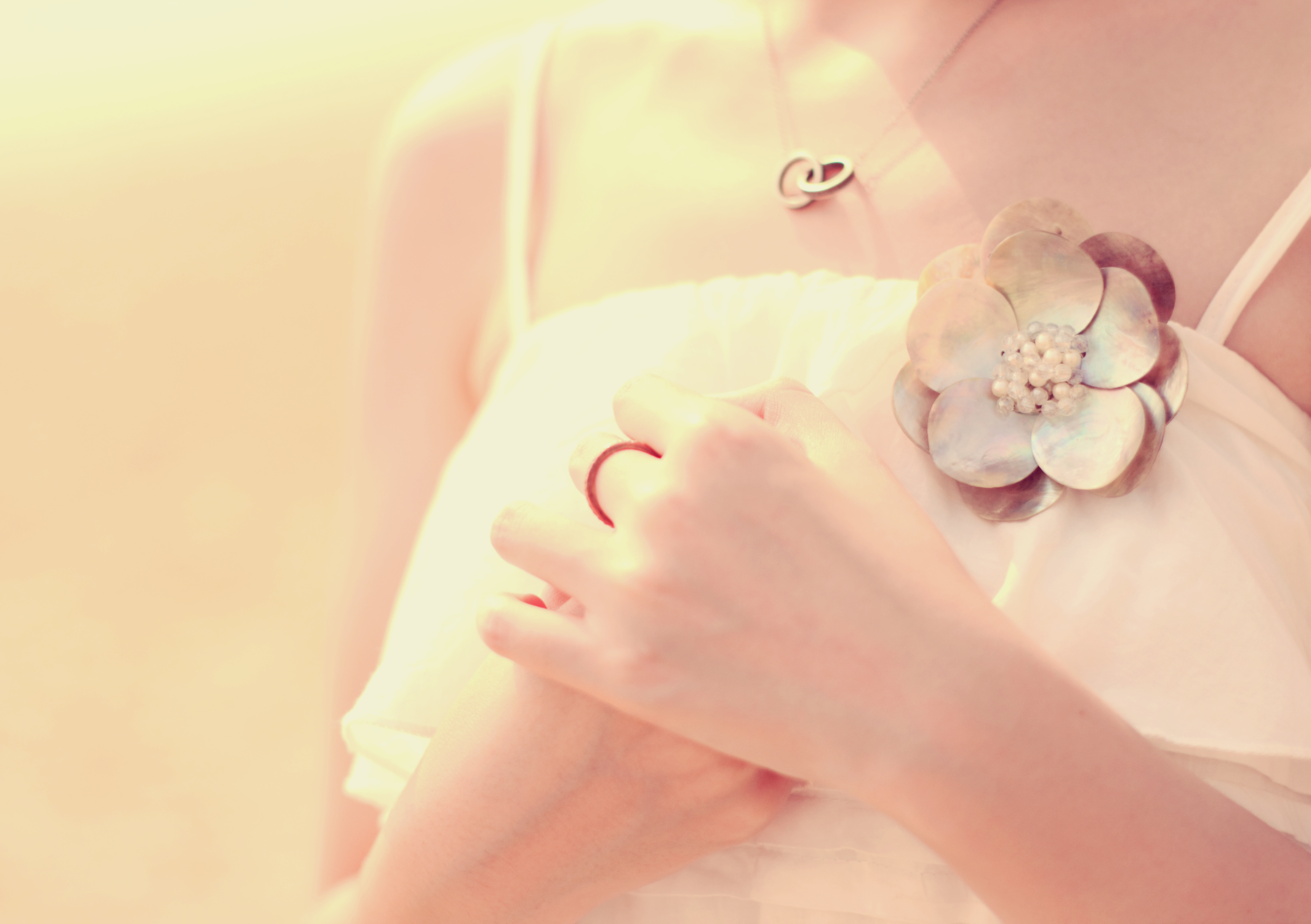 Close up of bride's hands with accessory for dress, retro filter effect