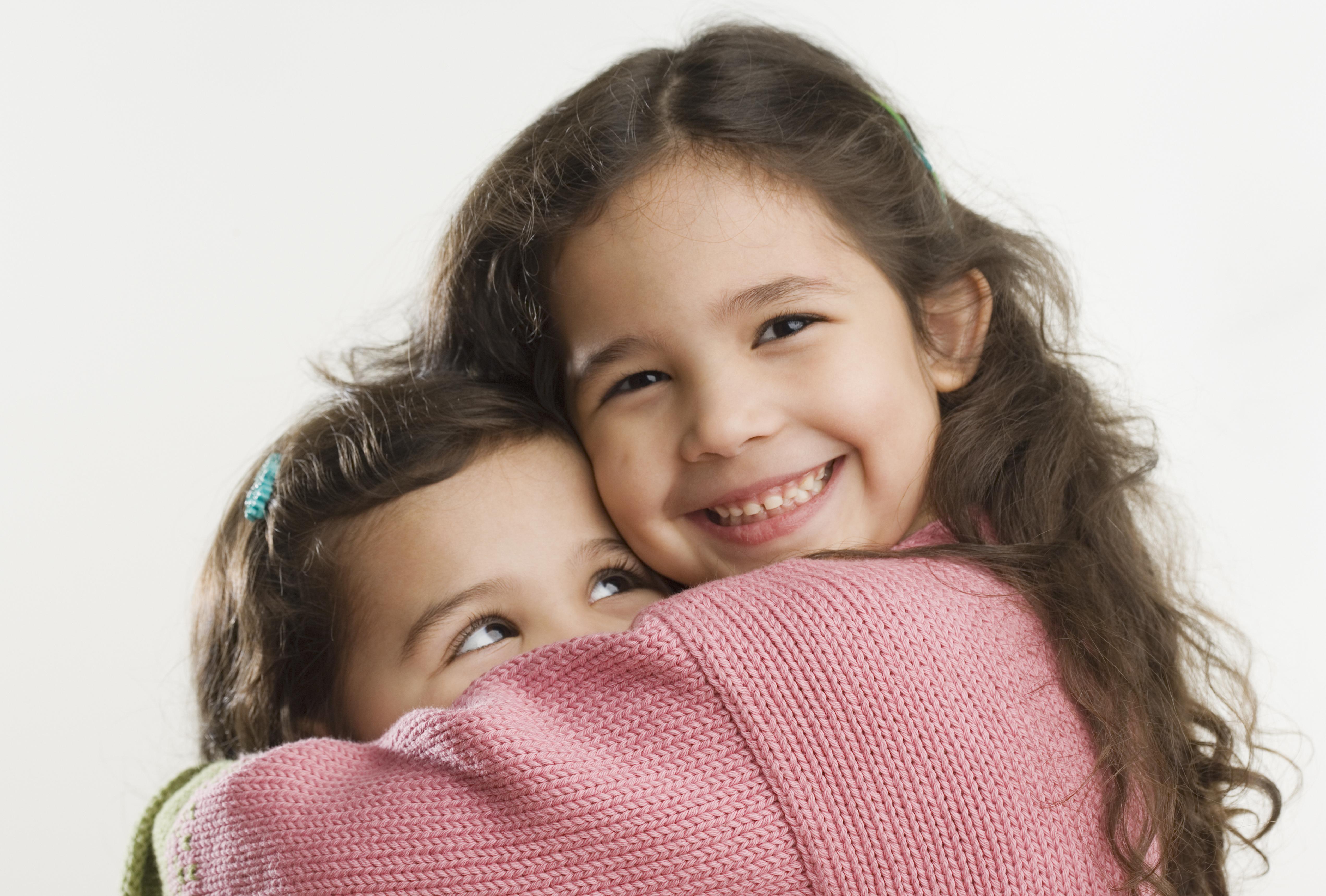 Studio shot of young Hispanic sisters hugging