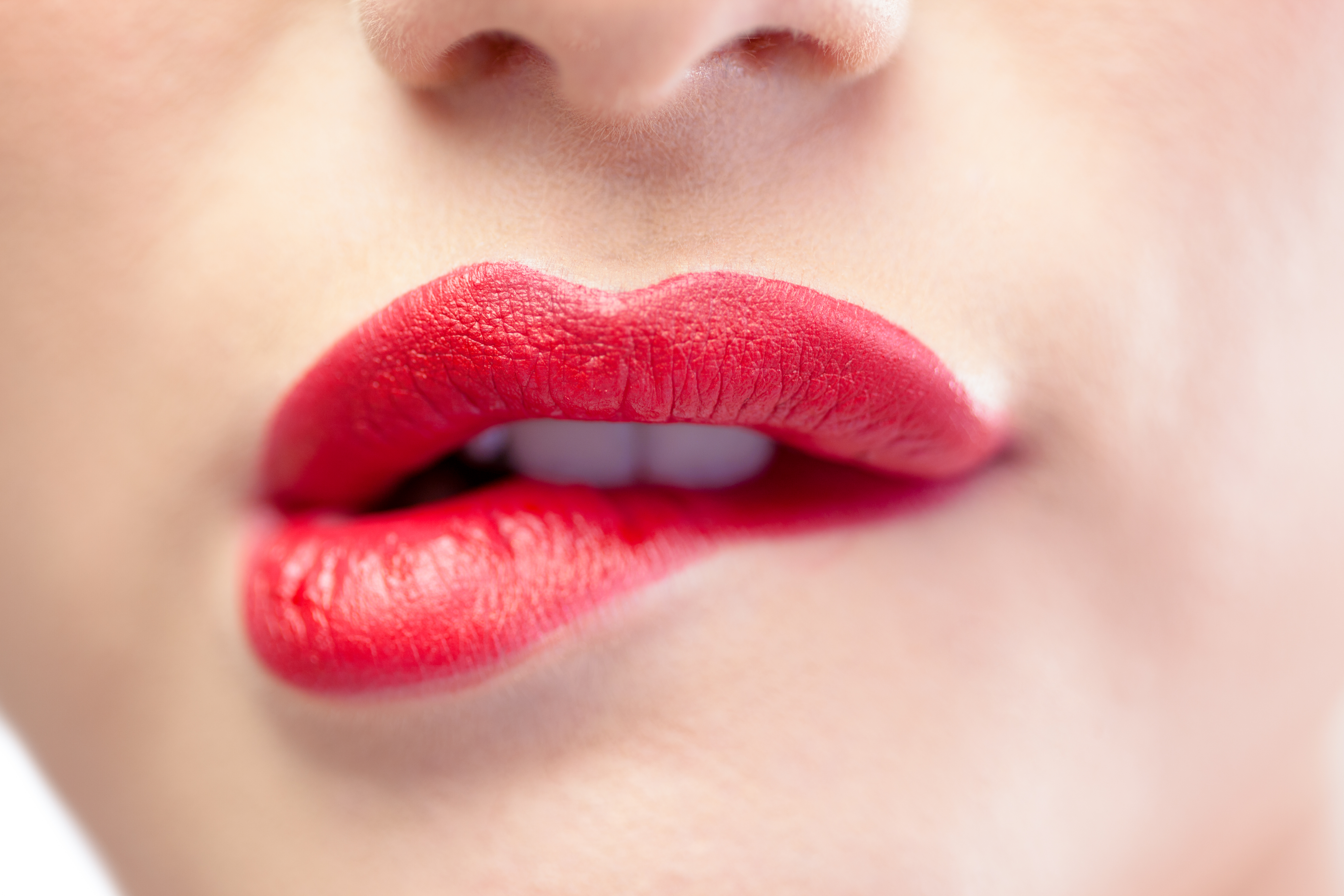 Close up on sensual model biting red lips on white background