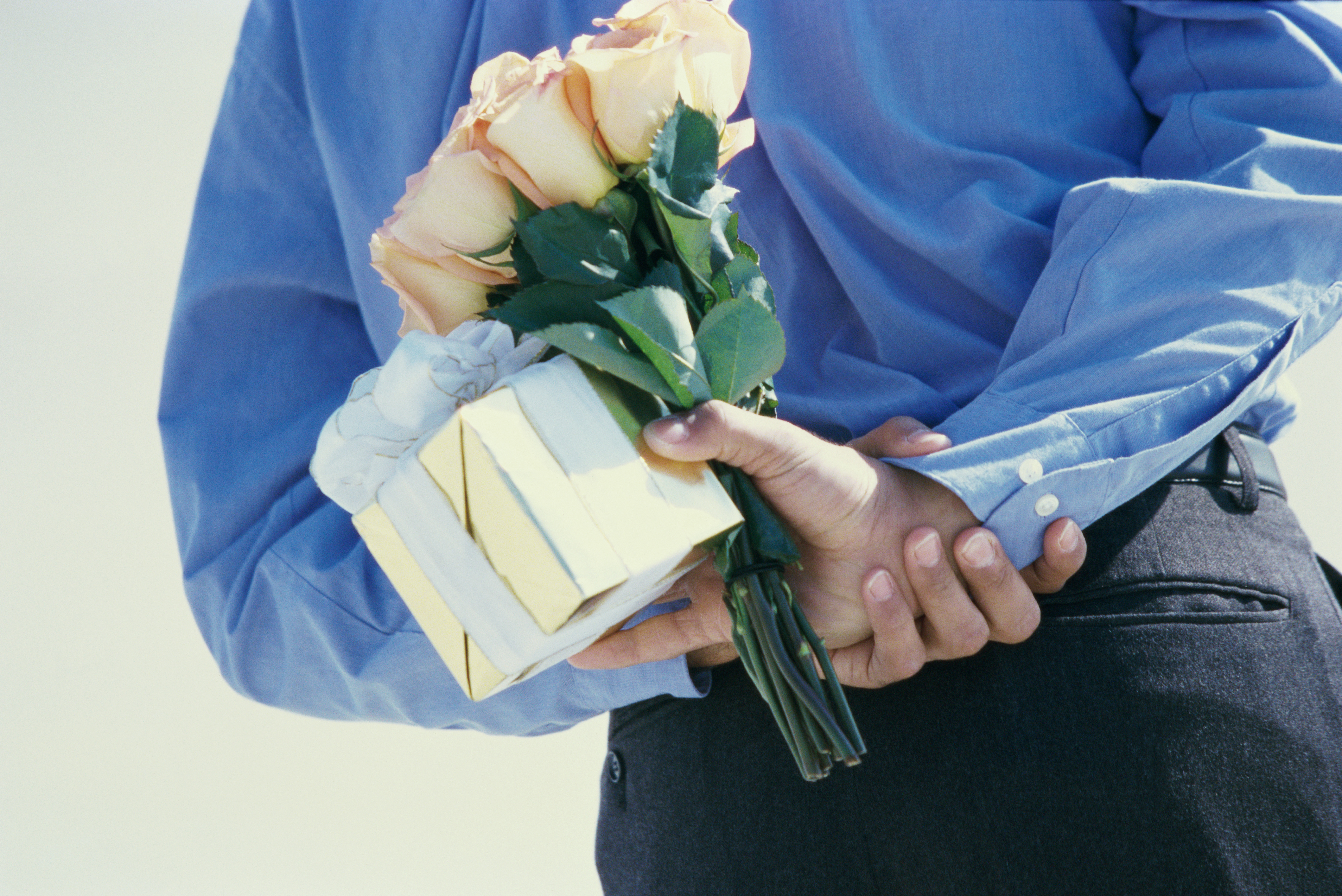 Rear view of a young man hiding flowers and a gift behind his back