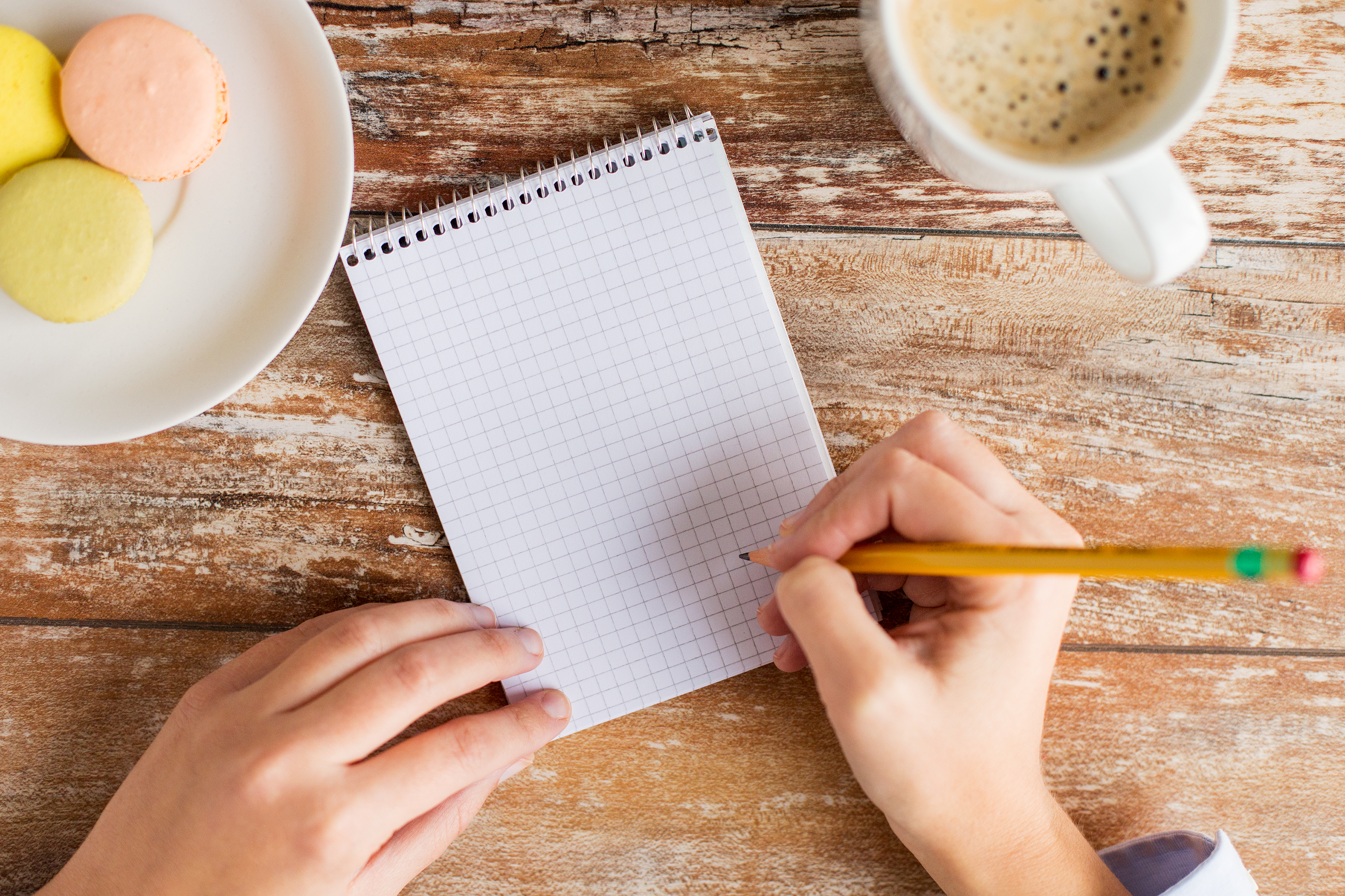 business, education and people concept - close up of female hands with with notebook, pencil, coffee and cookies on table
